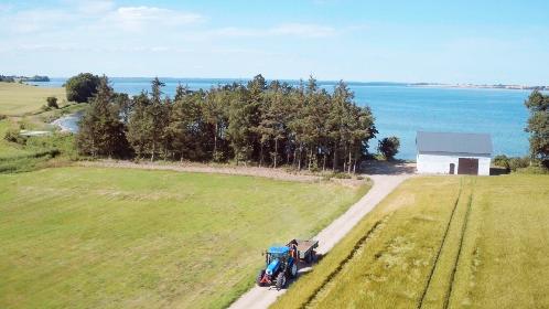 Traktor der kører fra gård