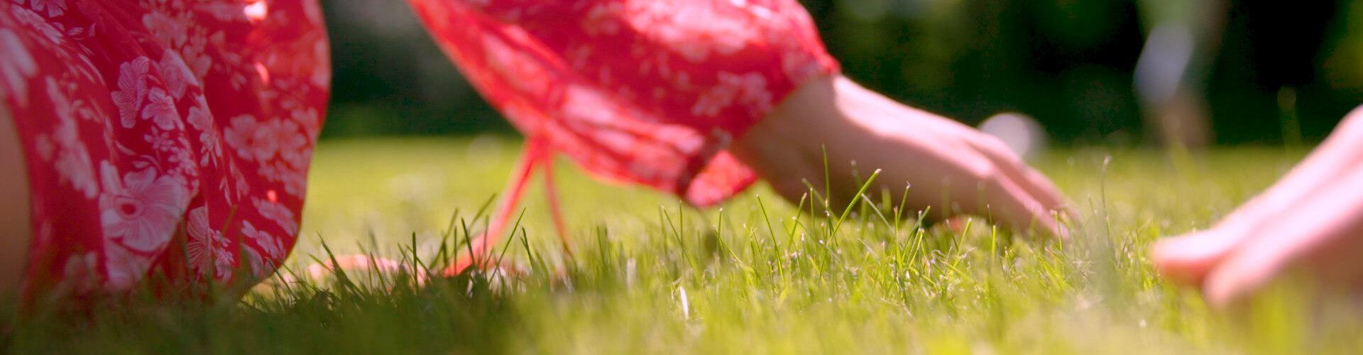Pige iført rød kjole sidder på det grønne græs